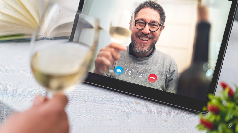 Two people during a Skype call with wine