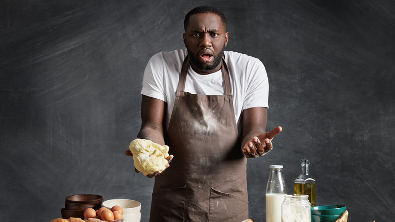 A man trying to cook, looking confused