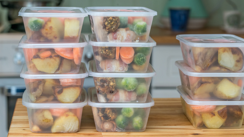 Filled meal prep containers stacked up, containing meals and snacks