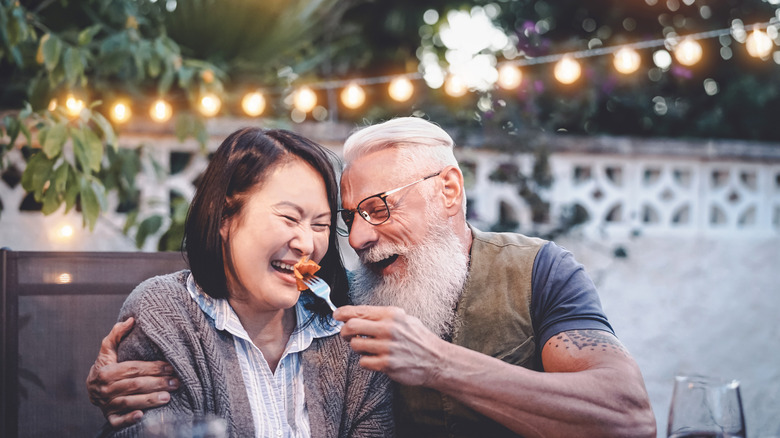 Two older adults laughing at the dinner table