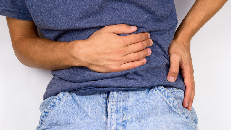 Person gripping their stomach, keeled over