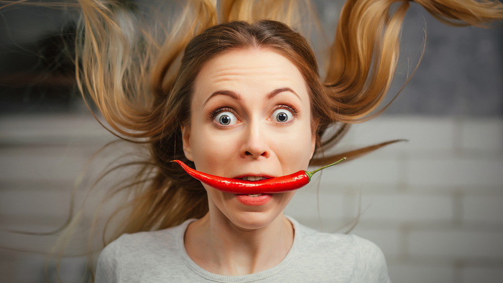 woman with spicy pepper in mouth